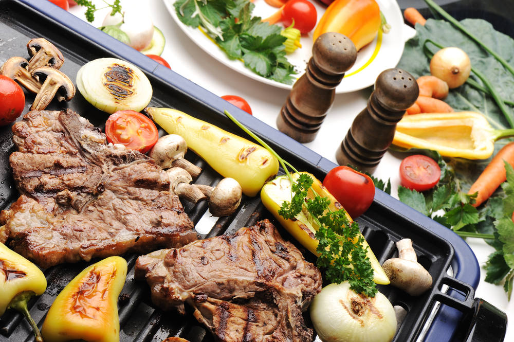 Barbecue, prepared beef meat and different vegetables and mushrooms on grill