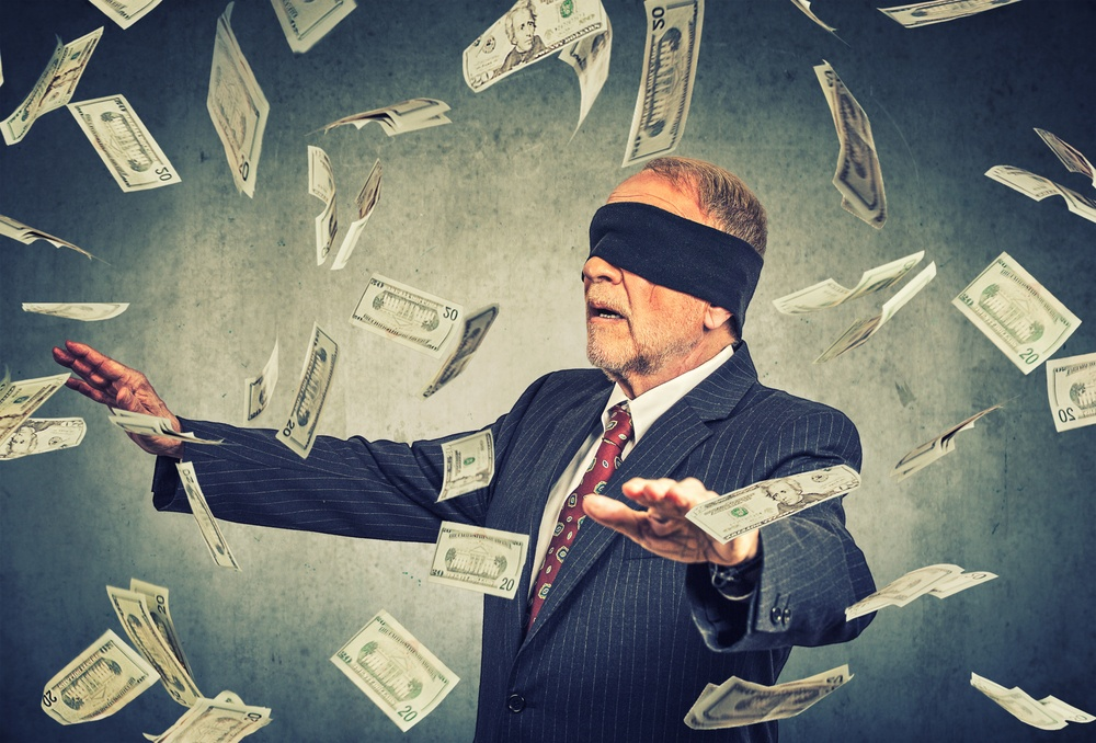 Blindfolded senior businessman trying to catch dollar bills banknotes flying in the air on gray wall background. Financial corporate success or crisis challenge concept-1