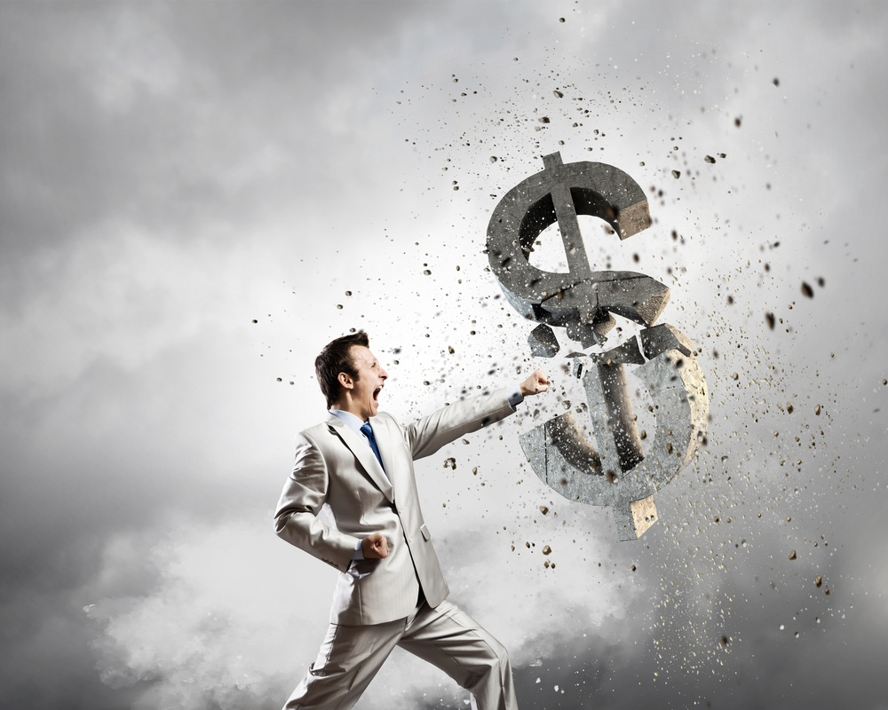 Businessman breaking stone dollar symbol with karate punch.jpeg