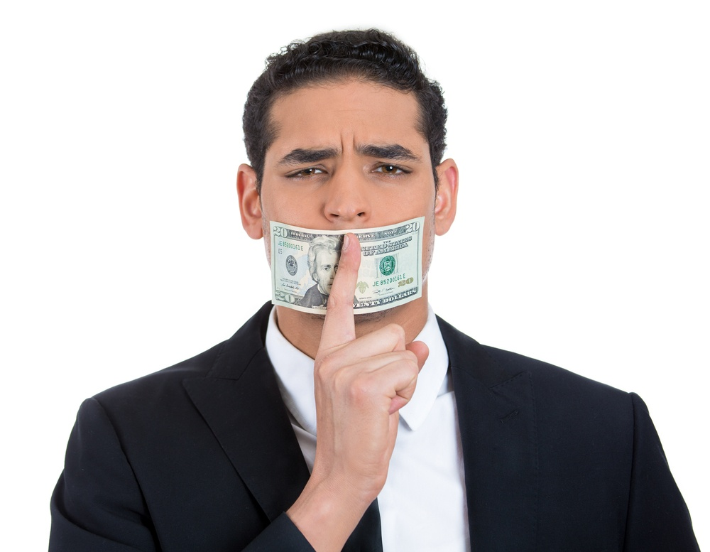 Closeup portrait of handsome corrupt guy in black suit with twenty dollar bill taped to mouth and showing shhh sign, isolated on white background. Bribery concept in politics, business, and diplomacy.
