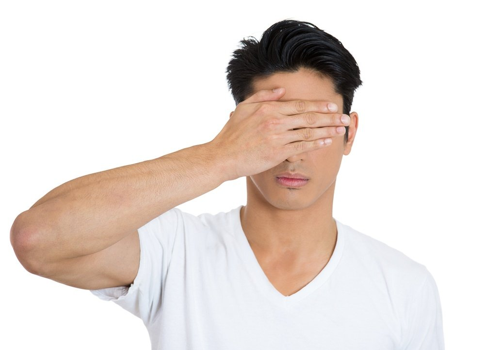 Closeup portrait of young man, closing, covering blind eyes with hands can't see, hiding, avoiding situation, isolated on white background. See no evil concept. Human emotions, facial expressions