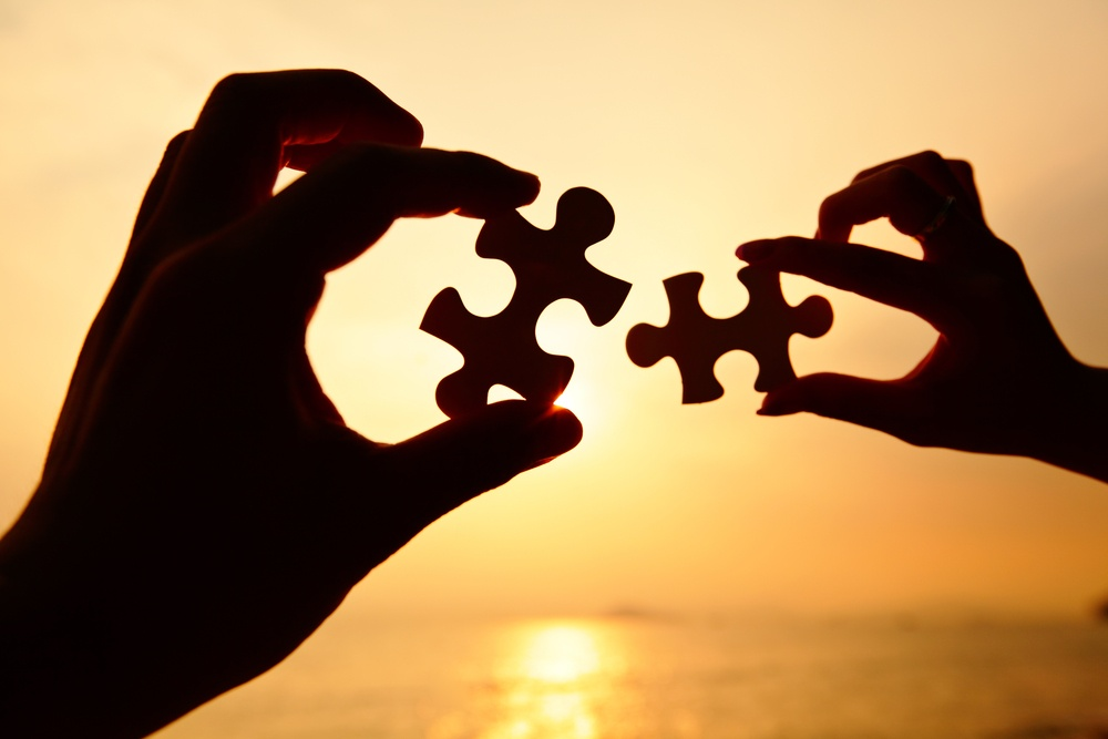 Man and woman hands trying to connect puzzle pieces