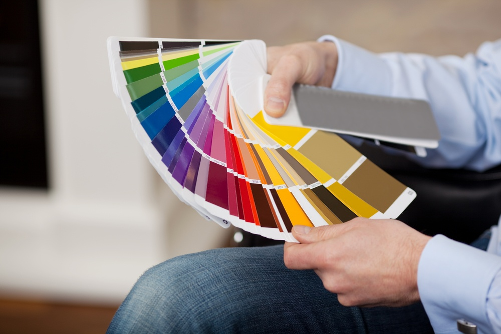 Man holding a set of paint color swatches in all the colors of the spectrum splayed out in his hand as he tries to decide on a new color for his house