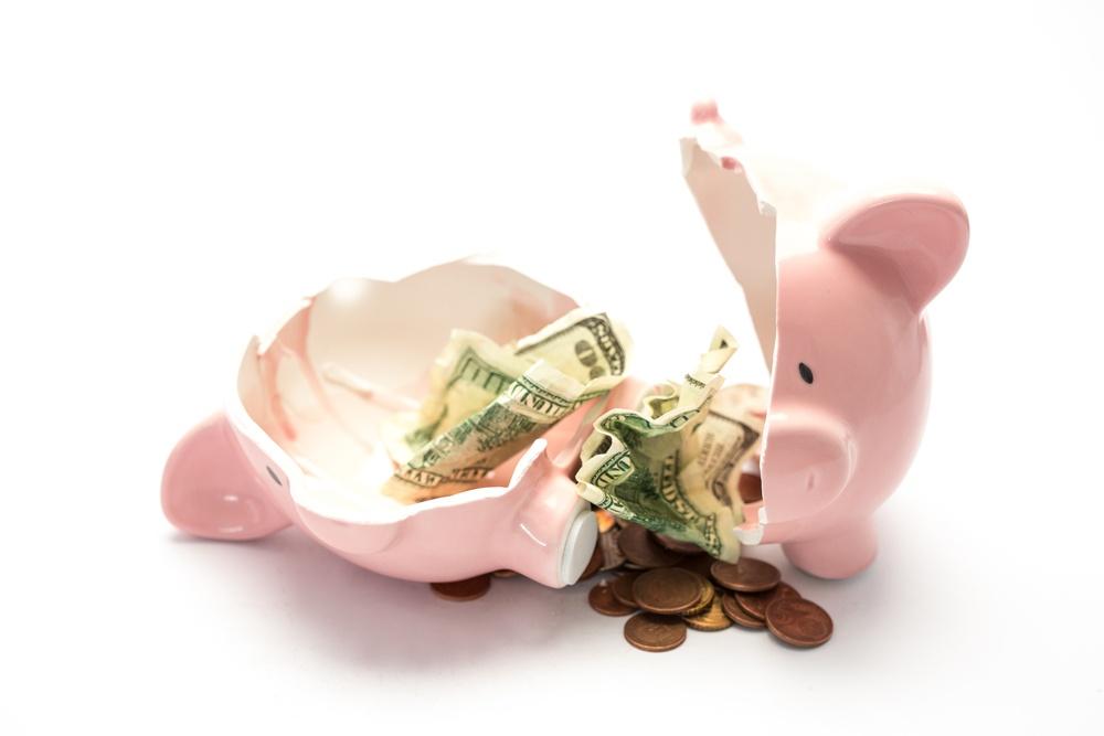 Piggy bank broken with money inside on white background