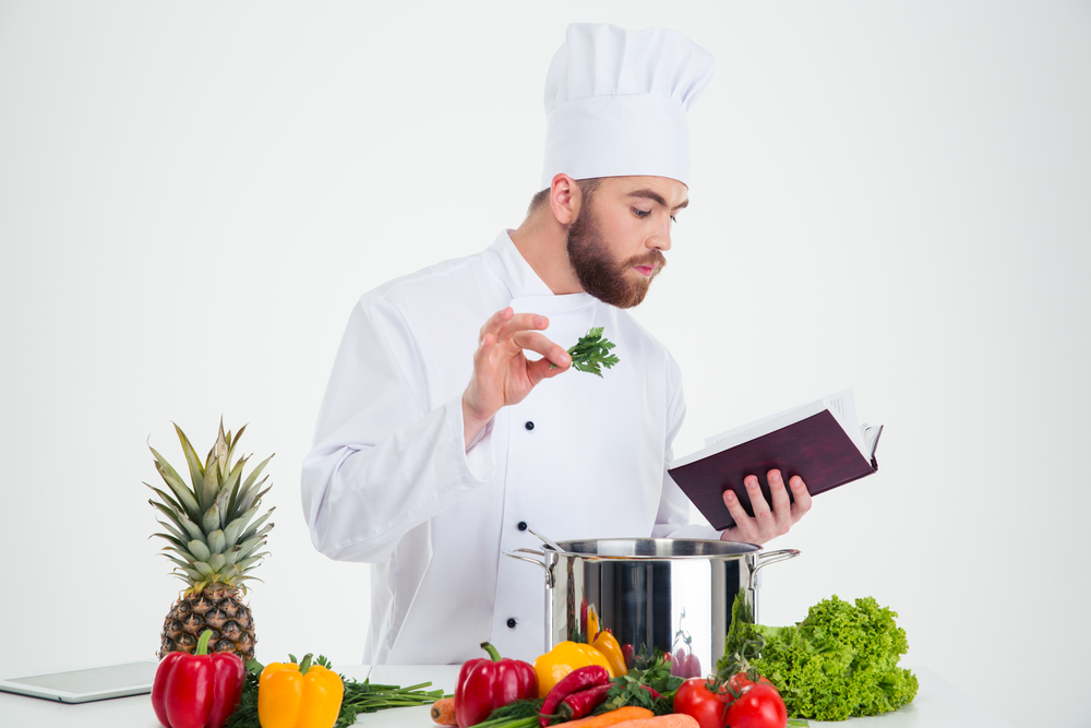 Portrait of a handsome male chef cook reading recipe book while preparing food isolated on a white background