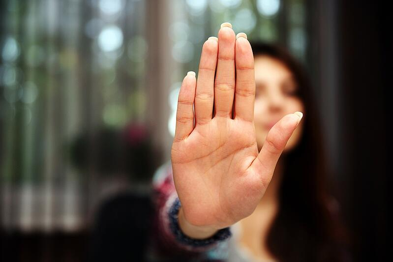 Woman with her hand extended signaling to stop (only her hand is in focus)-1