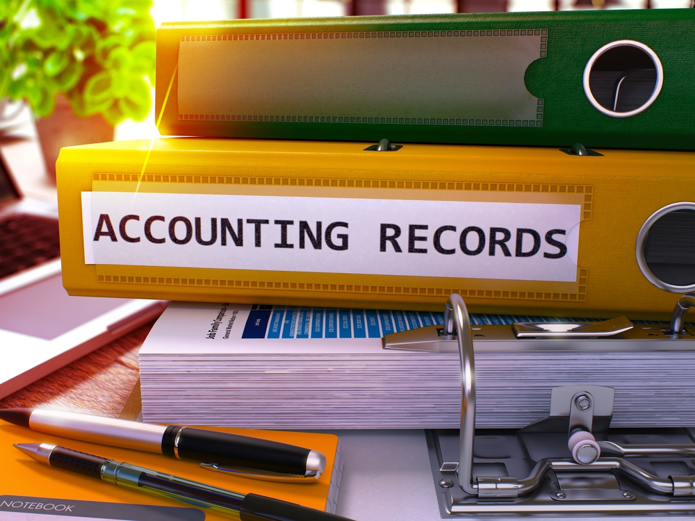 Accounting Records - Yellow Ring Binder on Office Desktop with Office Supplies and Modern Laptop. Accounting Records Business Concept on Blurred Background. 3D Render..jpeg