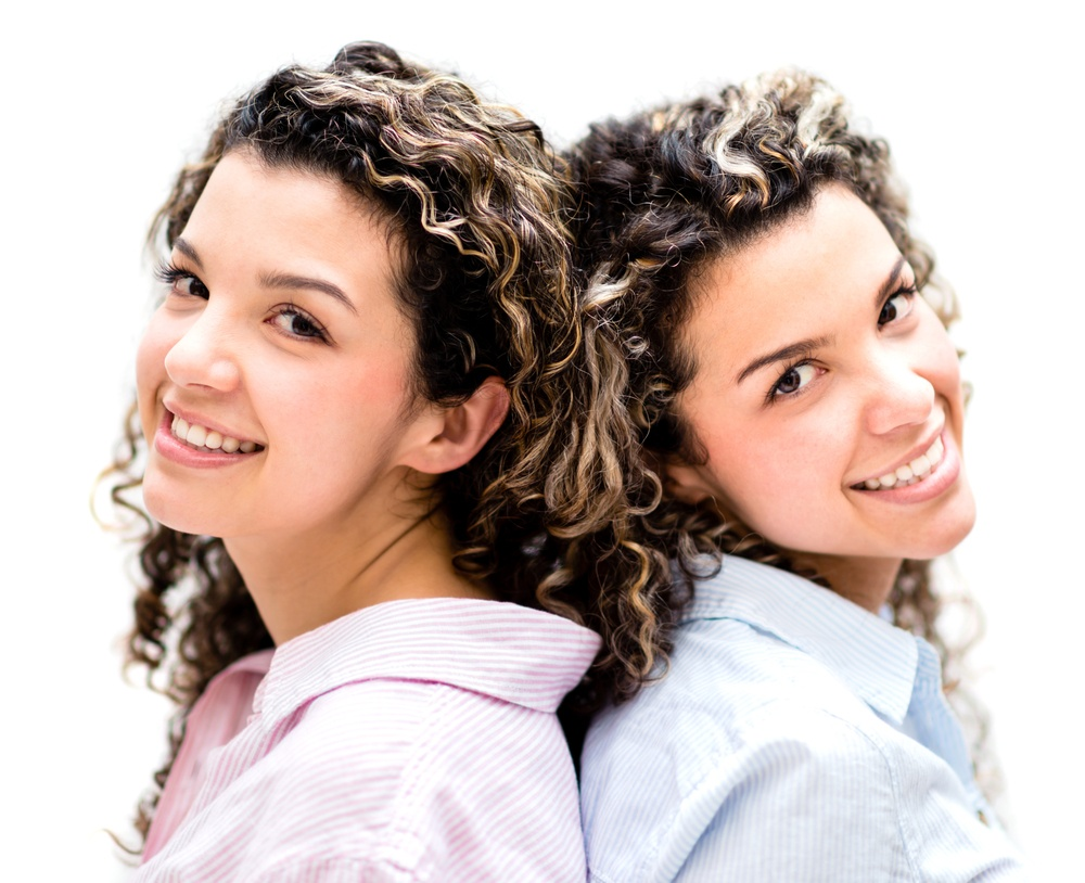 Beautiful twins smiling - isolated over a white background.jpeg