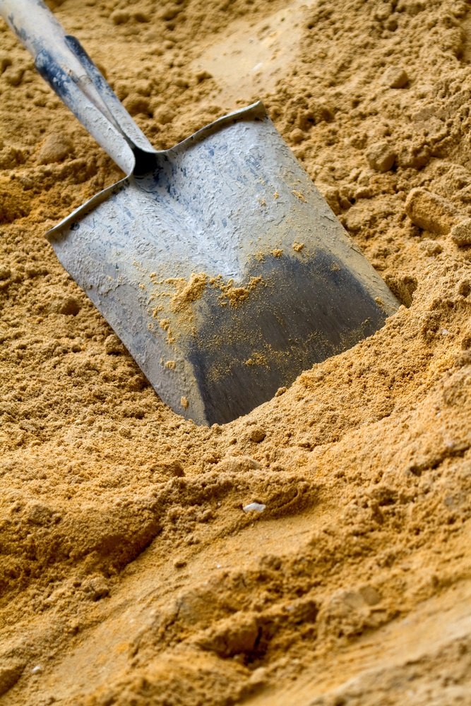 Construction shovel hammered in yellow sand - building materials.jpeg