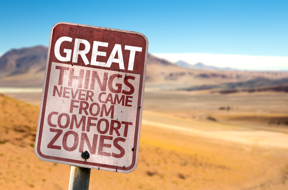 Great Things Never Came From Comfort Zones sign with a desert background.jpeg