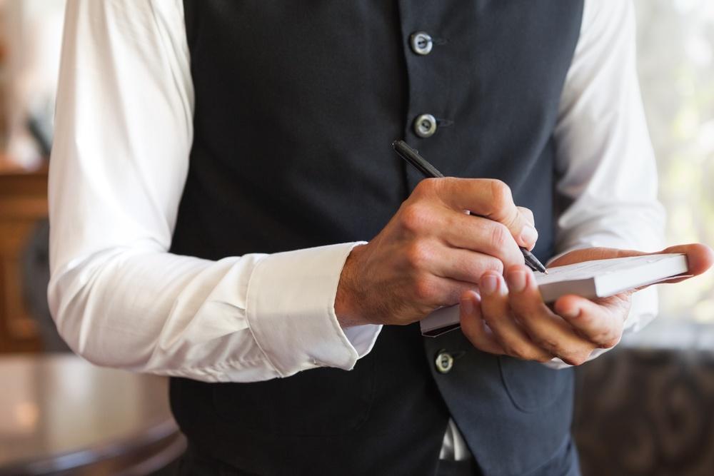 Waiter taking an order wearing a waistcoat in a fancy restaurant.jpeg
