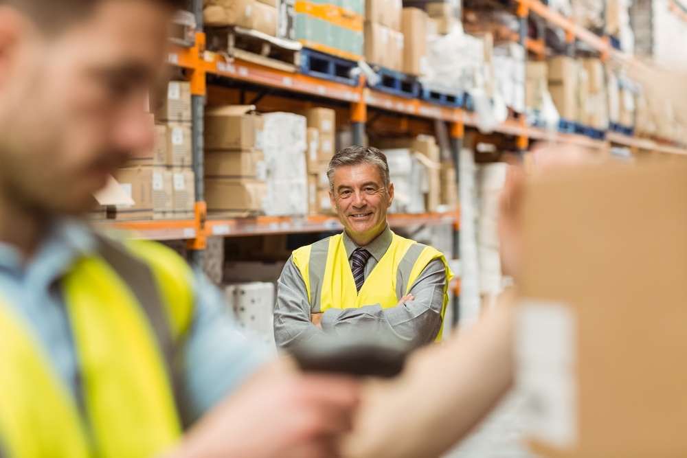 Warehouse worker scanning barcode on box in a large warehouse.jpeg