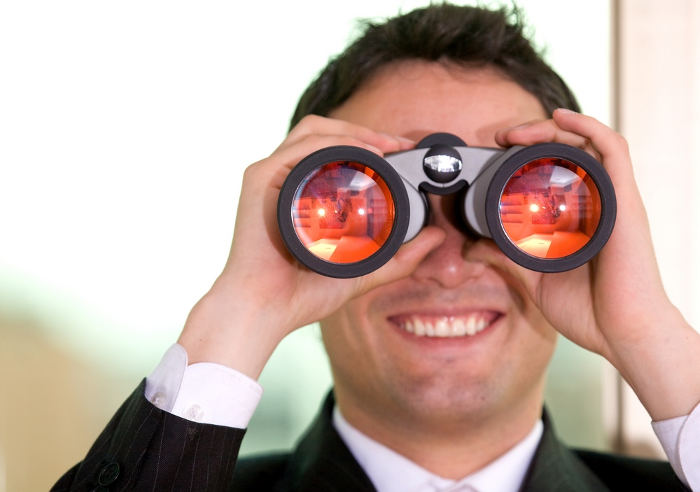 business man with a pair of binoculars in his office-1.jpeg